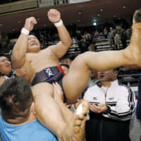 Koshiro Tanioka is hoisted into the air by supporters after winning the All Japan Championship, the country's top amateur sumo competition, at Ryogoku Kokugikan on Sunday. | KYODO