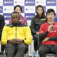 Yoshihide Kiryu (right) speaks at a news conference on Saturday at the new National Stadium. Usain Bolt (center) and other high-profile athletes and entertainers took part in events to welcome the public to the stadium for the first time. | KYODO