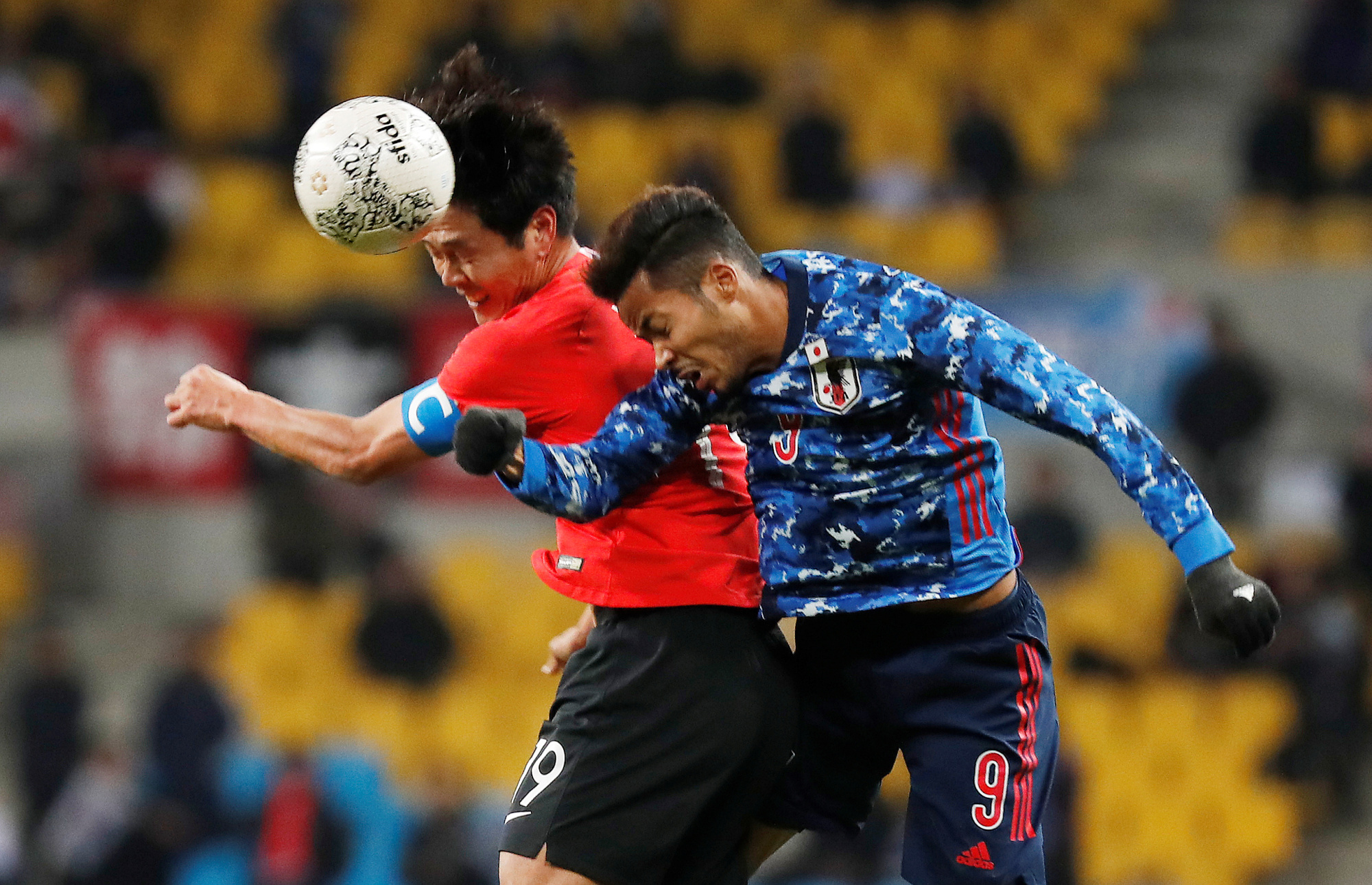 Japan's Musashi Suzuki (right) and South Korea's Kim Young-gwon vie for the ball during the men's final at the East Asian Football Federation E-1 Championship on Wednesday in Busan, South Korea. | REUTERS