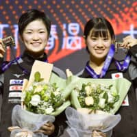 Miyu Kihara (left) and Miyu Nagasaki show off their medals after winning the women's doubles tourmanet at the ITTF World Tour Grand Finals on Sunday in Zhengzhou, China. | KYODO