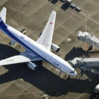 A chartered All Nippon Airways flight repatriating Japanese nationals from virus-hit Wuhan in China arrives at Haneda Airport in Tokyo on Wednesday. The airline said the same day it will extend throughout February the suspension of all flights between Wuhan and Narita International Airport in Chiba Prefecture. | KYODO