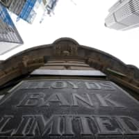 Signage is seen at the entrance to a branch of Lloyd's bank in the City of London financial district in London in 2017. | REUTERS