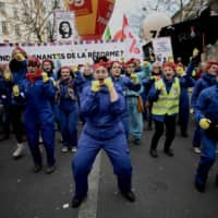 Feminist activists perform the 'Because of Macron' choregraphy as they march during a demonstration in Paris Jan. 11 as part as a nationwide multisector strike against the French government's pensions overhaul.   AFP-JIJI