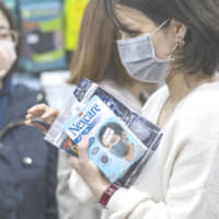 A customer shops for face masks at a pharmacy in the Central district of Hong Kong on Thursday. | BLOOMBERG