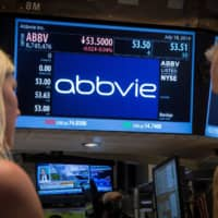 A screen displays the share price for pharmaceutical maker AbbVie on the floor of the New York Stock Exchange in 2014. | REUTERS