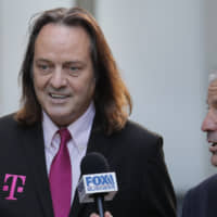 T-Mobile chief executive John Legere speaks to reporters as he leaves the courthouse in New York Wednesday. Legere was in court to hear closing arguments in the case that could permit T-Mobile to merge with Sprint. | AP