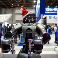 A robot produced by Toshiba Machine Co. is displayed at the International Robot Exhibition in Tokyo. A fund backed by activist investor Yoshiaki Murakami is launching a takeover bid for Toshiba Machine. | BLOOMBERG