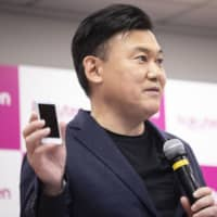 Hiroshi Mikitani, chairman and chief executive officer of Rakuten Inc., holds up a Rakuten Mini smartphone while speaking during a news conference in Tokyo on Sept. 6.   BLOOMBERG