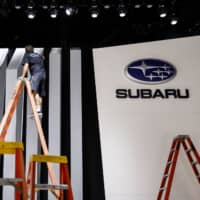 A worker cleans a wall at Subaru Corp.'s booth during preparations for the Los Angeles Auto Show in 2017. | BLOOMBERG