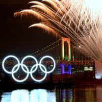 Fireworks go off near illuminated Olympic rings during a ceremony held to mark six months until the start of the Tokyo 2020 Olympics on Friday in the Odaiba district of Tokyo.  | SATOKO KAWASAKI