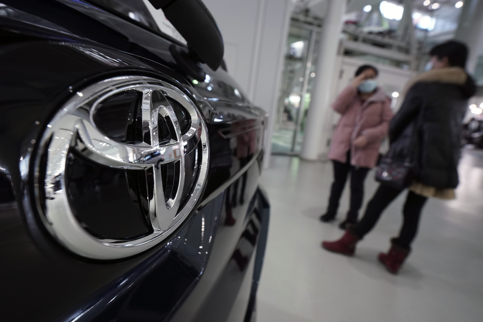 Visitors stand by a Toyota Motor. Co. car at a showroom on Thursday in Tokyo. German automaker Volkswagen AG has kept its lead as the world's largest automaker, selling more vehicles than Toyota last year. | AP