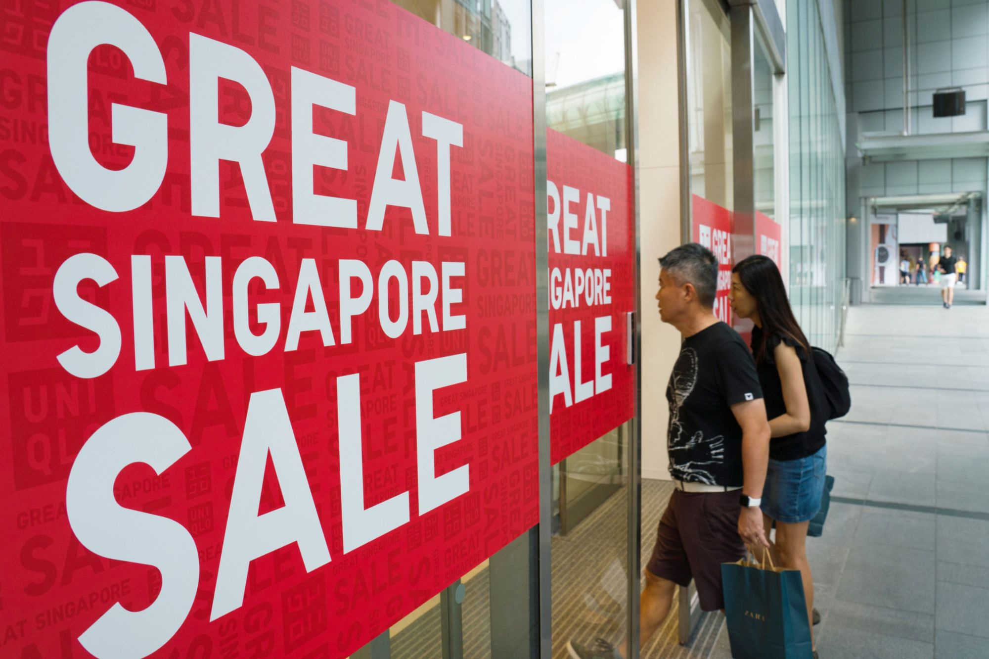 Sale posters are displayed at the entrance to a Uniqlo store in the Orchard Central shopping mall in Singapore. | BLOOMBERG