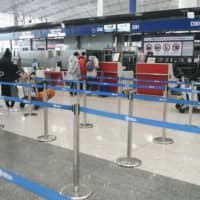 Check-in counters for Japan-bound flights are mostly quiet at Beijing Capital International Airport on Monday as a ban on group tours took effect. | KYODO