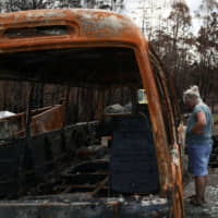 Alisha Stoneham returns to her property, where she and her partner were nearly caught in the flames before narrowly escaping, following the recent bushfires in Conjola Park, New South Wales, Australia, Tuesday. | REUTERS