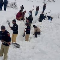 Police officers and local residents dig to search bodies of victims of avalanches in Doodnail village in Neelum Valley, Pakistan-administered Kashmir, Wednesday. | AP