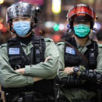 Riot police wear protective masks while standing guard on Nathan Street in the Mong Kok district of Hong Kong on Sunday. | BLOOMBERG