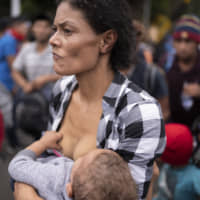 A migrant breastfeeds her baby as she walks with a group of migrants along a highway in hopes of reaching the distant United States, near Agua Caliente, Guatemala, Thursday on the border with Honduras. Hundreds of Honduran migrants started walking and hitching rides Wednesday from the city of San Pedro Sula, in a bid to form the kind of migrant caravan that reached the U.S. border in 2018. | AP
