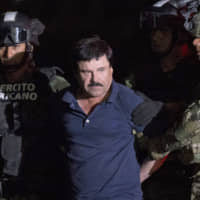 Mexican drug lord Joaquin 'El Chapo' Guzman is escorted by army soldiers to a waiting helicopter, at a federal hangar in Mexico City, after he was recaptured from breaking out of a maximum security prison in Mexico in 2016. Mexican President Andres Manuel Lopez Obrador closed out 2019 with a Tuesday video message that included a shot at his predecessors, saying imprisoned drug kingpin 'El Chapo' had had the same power as the country's president. | AP