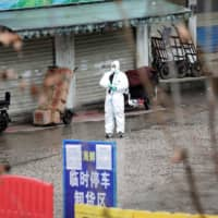 A worker in a protective suit is seen at the closed seafood market in Wuhan, Hubei province, China Jan. 10. The seafood market is linked to the outbreak of the pneumonia caused by the new strain of coronavirus, but some patients diagnosed with the new coronavirus deny exposure to this market.