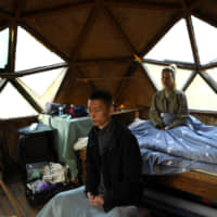 Yang Zhaoyu and Chen Yan meditate in the early morning inside a dome-shaped house on a hill at AnotherCommunity in the village of Guanzhong in China's Fujian province on Nov. 3.   REUTERS