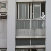 A medical staff member is seen by a window at the Jinyintan hospital, where patients with pneumonia caused by the new strain of coronavirus are being treated, in Wuhan, Hubei province, China, Jan. 20. | REUTERS