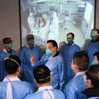 Chinese Premier Li Keqiang (center) speaks to medical workers at the Jinyintan hospital, where patients of a new coronavirus are being treated, in Wuhan on Monday. | REUTERS