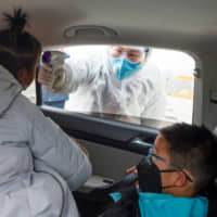 A medical worker checks the body temperature of a car passenger at a checkpoint outside the city of Yueyang, Hunan Province, on Tuesday. | REUTERS