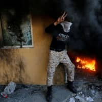A member of Hashd al-Shaabi (paramilitary forces) flashes the victory sign as he stands next to a reception room of the U.S. Embassy in Baghdad during a fiery protest to condemn airstrikes on bases belonging to Hashd al-Shaabi, in Baghdad Tuesday.   REUTERS