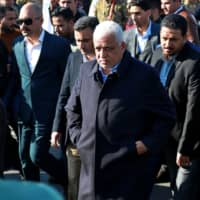 Iraqi National Security Adviser Faleh al-Fayadth (center) joins Iran-backed Popular Mobilization Forces as they enter the heavily fortified Green Zone, the seat of Iraq's government and the U.S. Embassy in Baghdad Tuesday. Dozens of angry Iraqi Shiite militia supporters broke into the embassy compound after smashing a main door and setting fire to a reception area.   AP