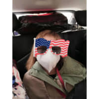 Hermoine Dickey, 8, rides in a car on her way to Wuhan Tiange International Airport for a U.S. evacuation flight Tuesday. The U.S. government is chartering a flight to transport several hundred diplomats, family members, and other Americans out of Wuhan, the central Chinese city at the heart of a new virus outbreak. | PRISCILLA DICKEY / VIA AP