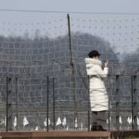 A visitor looks over a military fence on a viewing deck at Imjingak peace park, near the Demilitarized Zone (DMZ) dividing the two Koreas, in Paju, South Korea, Wednesday. In a statement reported by North Korea's state media, leader Kim Jong Un has declared an end to moratoriums on nuclear and intercontinental ballistic missile tests and threatened a demonstration of a 'new strategic weapon' soon. | AFP-JIJI