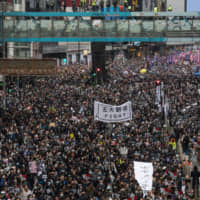 Hong Kongers protest in the Causeway Bay district on Wednesday. | BLOOMBERG