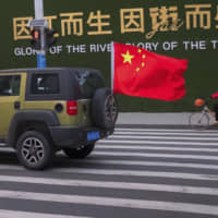 A vehicle flying a Chinese flag drives past a woman wearing a face mask as she rides a bicycle along a street in Wuhan in central China's Hubei Province Wednesday. Countries began evacuating their citizens Wednesday from the Chinese city hardest-hit by a new virus that has now infected more people in China than were sickened in the country by SARS. | AP