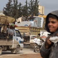 Syrians arrive in trucks transporting their belongings to Hazano in the northern countryside of Idlib city Monday after fleeing its southern countryside during an ongoing offensive by regime forces on the northwestern region. | AFP-JIJI