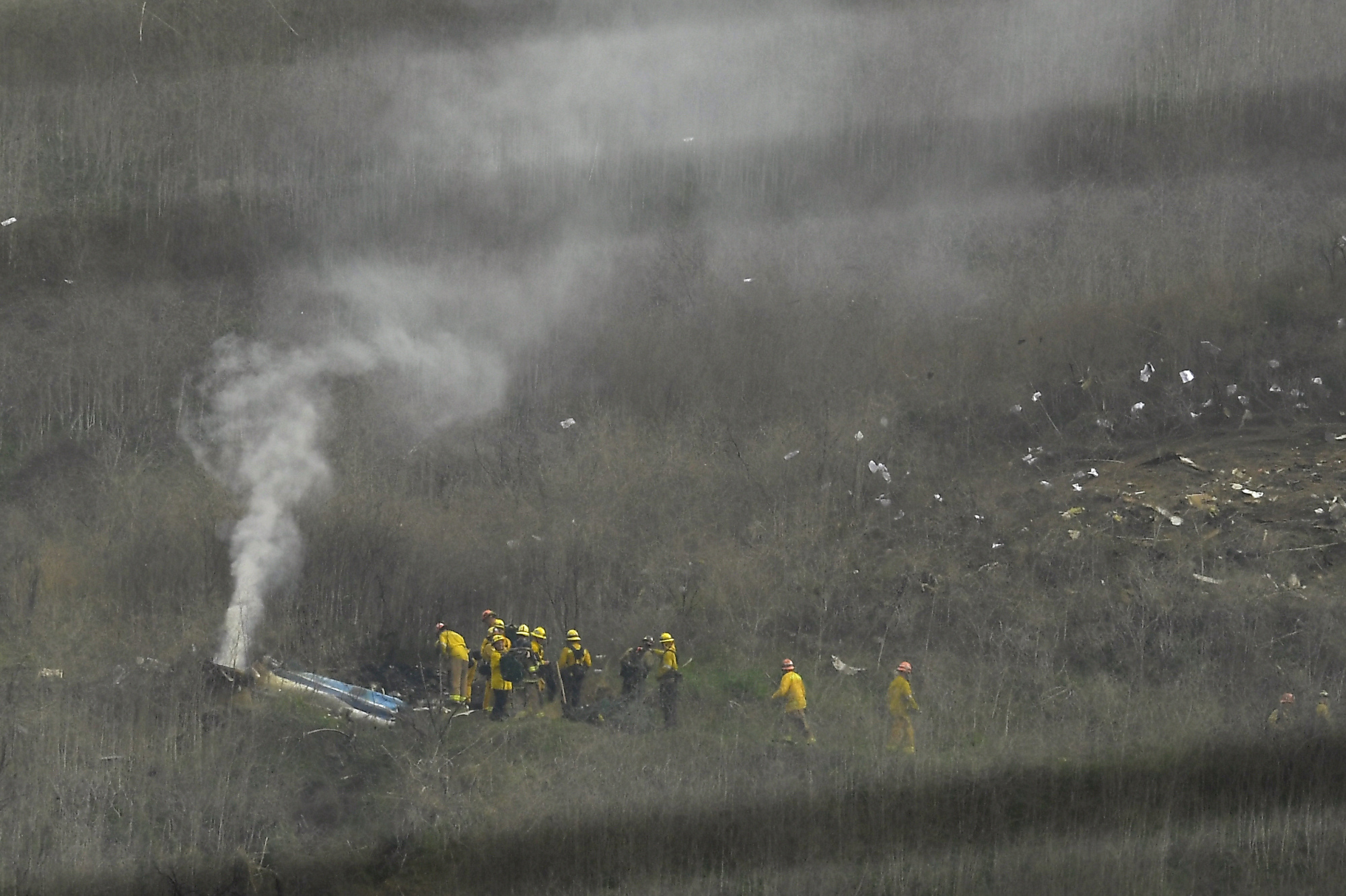 Firefighters work the scene of a helicopter crash that killed former NBA basketball player Kobe Bryant Sunday in Calabasas, California.   AP