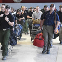 A contingent of 39 firefighters from the United States and Canada arrive at the airport in Melbourne on Thursday. The firefighters will assist local crews with ongoing fires burning across the state of Victoria. | AP