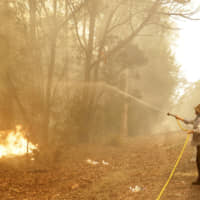 A man uses a water hose to battle a fire near Moruya, Australia, Saturday. Australia's prime minister Scott Morrison called up about 3,000 reservists as the threat of wildfires escalated Saturday in at least three states with two more deaths, and strong winds and high temperatures were forecast to bring flames to populated areas including the suburbs of Sydney. | AP