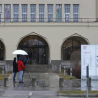A television crew films outside the Schwabing hospital, where four people are being treated for coronavirus, as snow falls in Munich, Germany, on Wednesday. Governments tightened international travel and border crossings with China to try to stop the spread of a coronavirus outbreak that has sickened thousands, and Germany said it had identified a cluster of local patients infected by a woman from Shanghai who had been visiting Europe.   BLOOMBERG