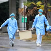 Medical staff carry a box as they walk at the Jinyintan hospital, where the patients with pneumonia caused by the new strain of coronavirus are being treated, in the Chinese city of Wuhan on Jan. 10. | REUTERS