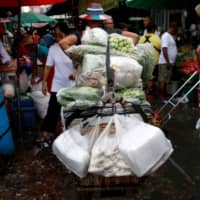 Vendors sell vegetables from plastic bags at a market in Bangkok in June. | REUTERS