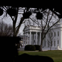 The White House is seen Thursday beyond television equipment in Washington. House Speaker Nancy Pelosi and Senate Majority Leader Mitch McConnell are locked in a stare-down over the terms of President Donald Trump's impeachment trial, which carries political risks for both sides if it continues deeper into January. | BLOOMBERG