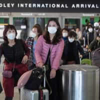 Passengers wear masks to protect against the spread of the coronavirus as they arrive on a flight from Asia at Los Angeles International Airport on Wednesday. Many countries across the globe are now wondering how they should deal with Chinese tourists, as fear of the potentially deadly disease spreads. | AFP-JIJI