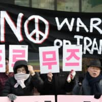 South Korean activists near the U.S. Embassy in Seoul on Tuesday hold placards reading 'No dispatch to Hormuz!' during a rally denouncing the government's decision to send troops to the Middle East. | AFP-JIJI