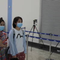 Chinese passengers wearing face masks walk past a thermal scanner set up to check the temperature of passengers at Colombo International airport in Colombo Saturday. | AP