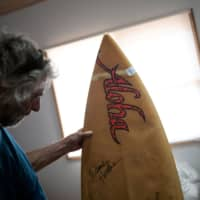 David Ford shows one of the few unburned surfboards from his vintage collection on Wednesday in Lake Conjola, Australia. | REUTERS