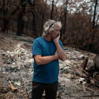 David Ford stands next to the burned shed where he kept his vintage surfboards. | REUTERS