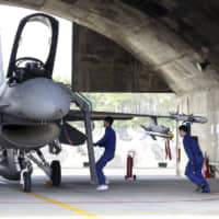 Ground crew of the Taiwan air force run to a U.S. made F-16V fighter for its emergency takeoff during a military exercise in Chiayi County, southern Taiwan, Wednesday. Taiwan military started a two-day joint forces exercises on Wednesday to show its determination to defend itself from Chinese threats. | AP