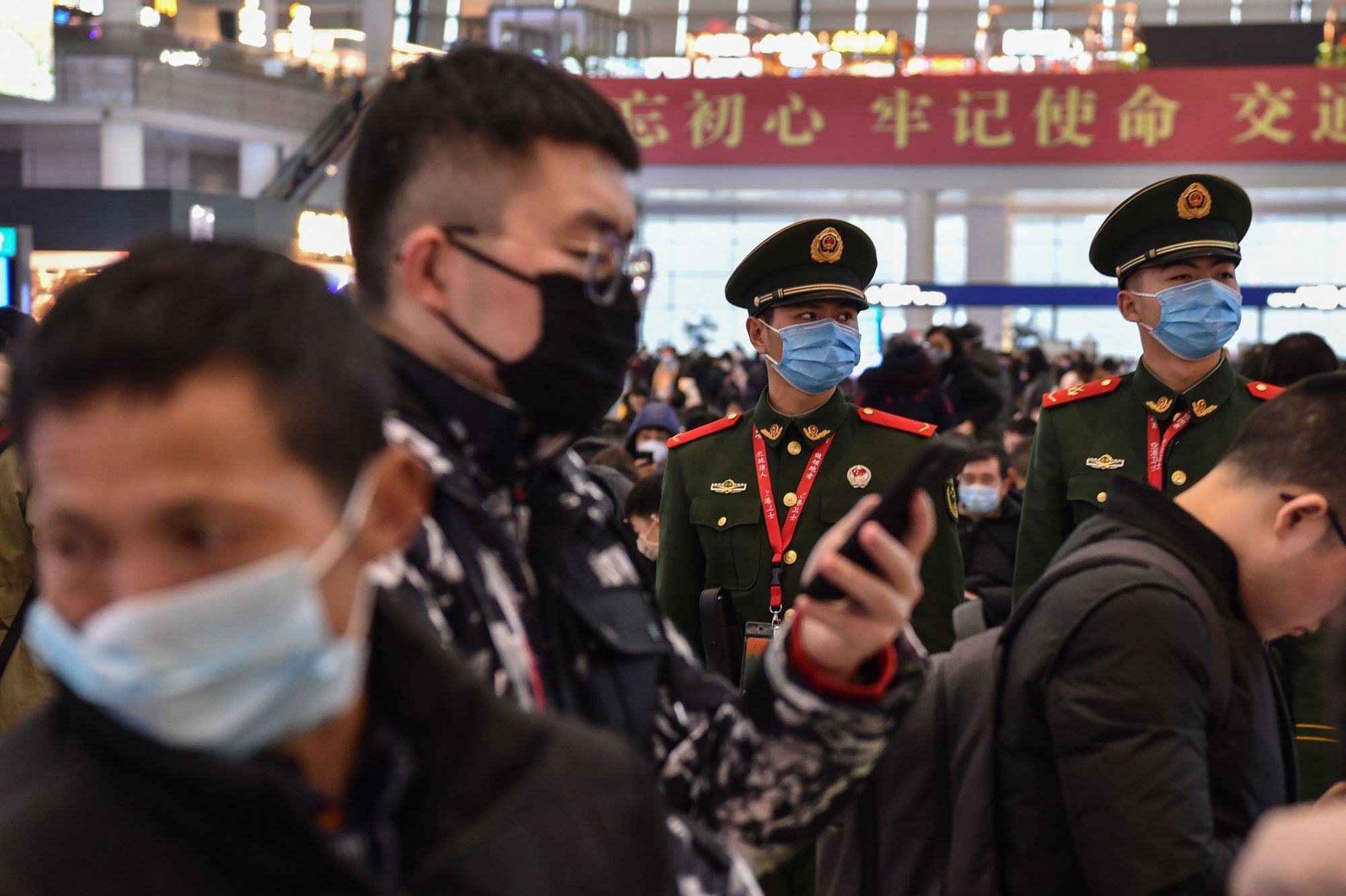 Chinese paramilitary police wearing masks stand guard while people wait for their train at Hongqioa station as they head home for the Lunar New Year in Shanghai on Thursday.  | AFP-JIJI