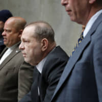 Harvey Weinstein (third from left) leaves court in New York Monday. The disgraced movie mogul faces allegations of rape and sexual assault. | AP
