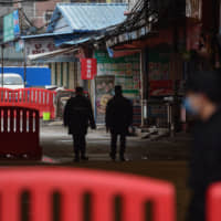 Security guards patrol outside the Huanan Seafood Wholesale Market in Wuhan, the epicenter of the outbreak of the new coronavirus, on Friday.   AFP-JIJI